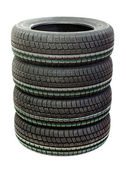 Four new tires stacked on white background — Stock Photo