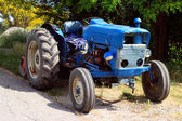 Old blue tractor on the road — Foto Stock