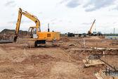 Excavadora amarilla en un sitio de construcción — Foto de Stock