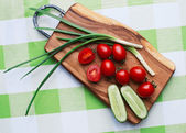 Red tomatoes and green onions on cutting board closeup — Zdjęcie stockowe