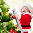Christmas baby on a step ladder — Stock Photo