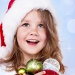 Preschool girl holding Christmas decoration — Stock Photo