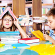 Girl and boy in a library — Stock Photo
