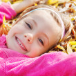Girl lying on yellow leaves — Stock Photo