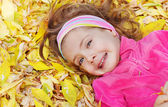 Child lying on leaves — Stock Photo