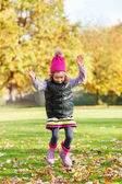 Girl jumping in autumnal park — Stock Photo