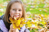 Preschool girl with yellow leaves — Stock Photo