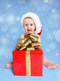 Little boy beside Christmas present — Stock Photo