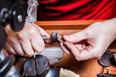 Jeweler polishes golden earring — Stock Photo