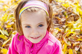 Girl over yellow autumn leaves — Stock Photo