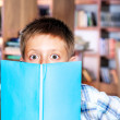 Boy hiding behind book — Stock Photo