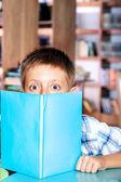 Boy hiding behind book — Stock Photo