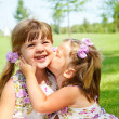 Girl kissing her sister - Foto de Stock