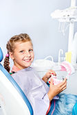 Girl cleaning toy dentures — Stock Photo
