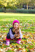 Child playing with yellow leaves — Stock Photo