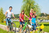 Parents and kids cycling — Stock Photo