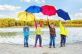 Boys and girls holding umbrellas — Stock Photo