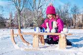Preschool girl making snowballs — Stock Photo