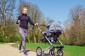 Jogging with a baby buggy — Stock Photo