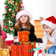 Kids sit beside Christmas presents — Stock Photo #8686522