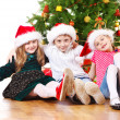 Kids in Santa hats embracing — Stock Photo #8686666