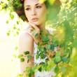 Young beauty among greenery — Foto Stock