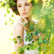 Foto Stock: Young beauty among greenery