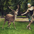 Young blonde lady running with deer - Stockfoto