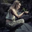 Beautiful young woman holding a plant — Stockfoto