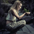 Beautiful young woman holding a plant - Stock Photo