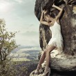 Blonde beauty posing on a dangerous rock — Foto Stock