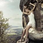 Blonde beauty posing on a dangerous rock — Stock Photo