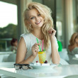 Young cheerful blonde in a drink bar — Stock Photo
