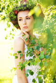 Young beauty among greenery — Stock fotografie