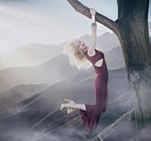 Attractive blonde lady hanging on a tree — Stock Photo