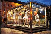 Many shopping women on exhibition window — Stock Photo
