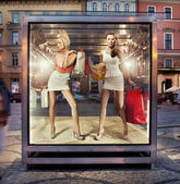 Two shopping women on exhibition window — Stok fotoğraf