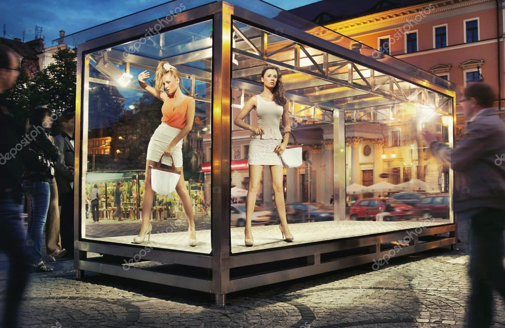 Two pretty good looking woman in exhibition window — Stock Photo #13878056
