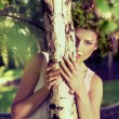 Beautiful girl behind the tree — Stock Photo