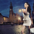 Sexy young beauty posing over night city background — Stock Photo