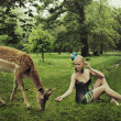 Adorable young lady playing with deer - ストック写真