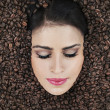 Beautiful face among coffee beans — Stock Photo