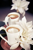 Cups of milk coffee with flowers — Stock Photo