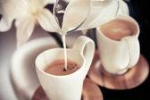 Two cups of coffee with decoration and poured milk — Stock Photo