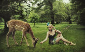 Adorable young lady playing with deer — Stock Photo