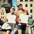 Two smiling girls holding empty board — Stock Photo