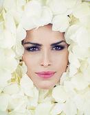 Beautiful woman face among rose petals — Stock Photo