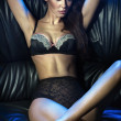 Voluptuous brunette on the sofa — Stok fotoğraf