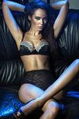 Voluptuous brunette on the sofa — Stock Photo