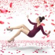Stock Photo: Attractive lady falling down over rose petals background